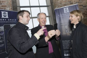 Bishop of Derry Rt Rev Dr Rev Good getting to grips with the Downhill app. Looking on are University of Ulster Learning Technologist Adrian Hickey and lecturer in Interactive Media, Helen Jackson.